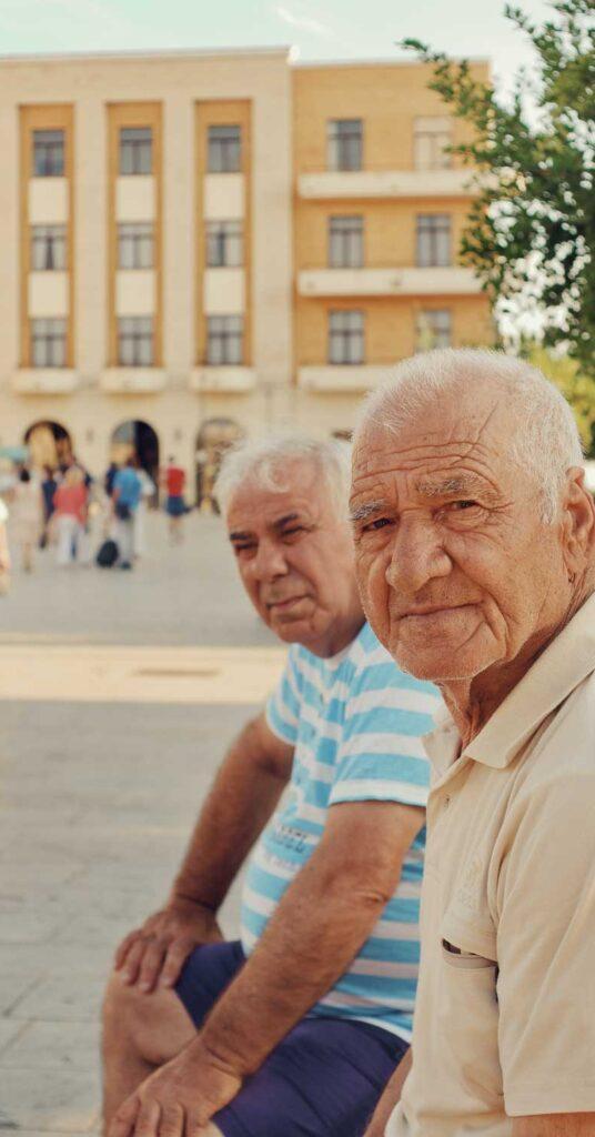 dois senhores aposentados sentado num banco na praça