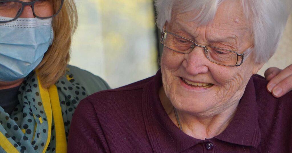 senhora aposentada pelo inss sorrindo ao ser mostrada algo no celular