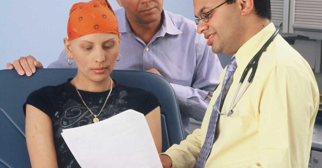paciente tratando câncer recebendo notcícia do médico acompanhada do marido
