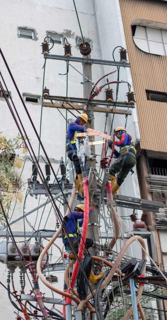 trabalhadores em condições de risco instalando distribuidoras de energia elétrica em um poste